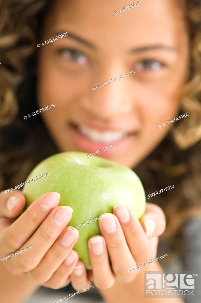 Stock Photo: Portrait of a girl holding a green apple and smiling.