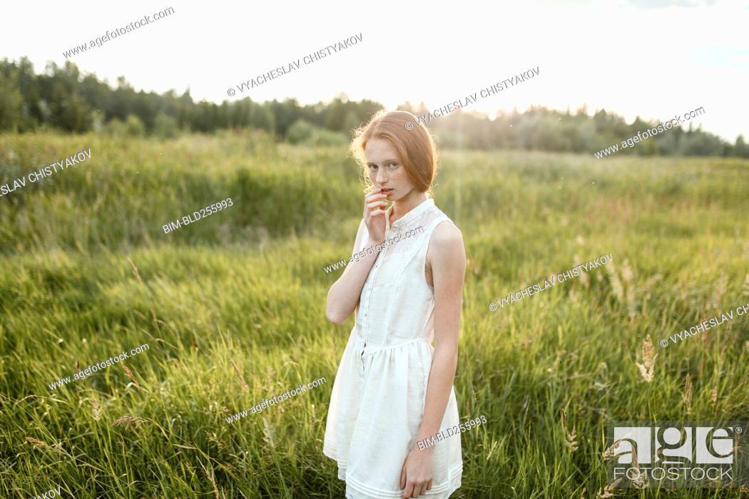 Stock Photo: Portrait of pensive Caucasian girl standing in field.