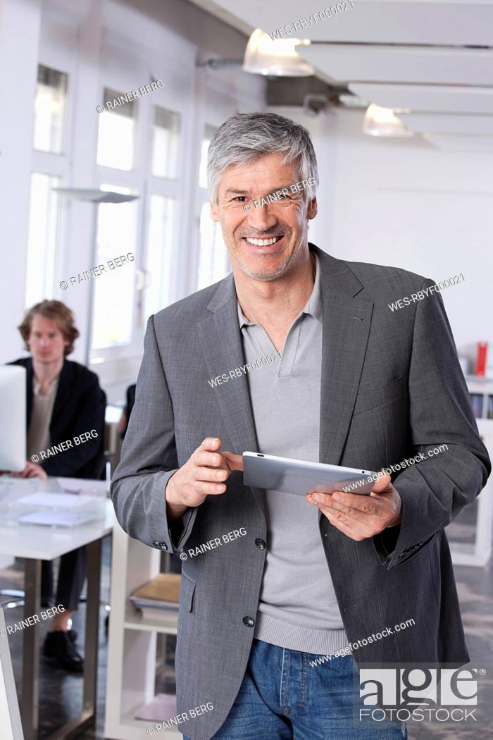 Stock Photo: Germany, Bavaria, Munich, Mature man using digital tablet, colleague working in background.