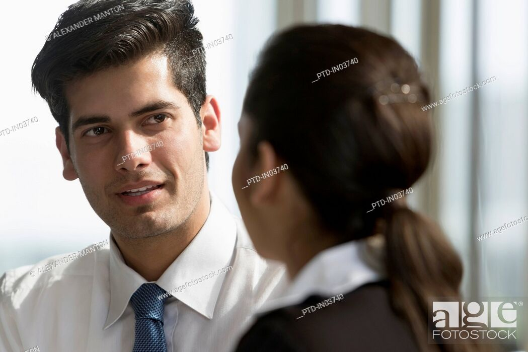 Stock Photo: Businessman talking to female colleague.