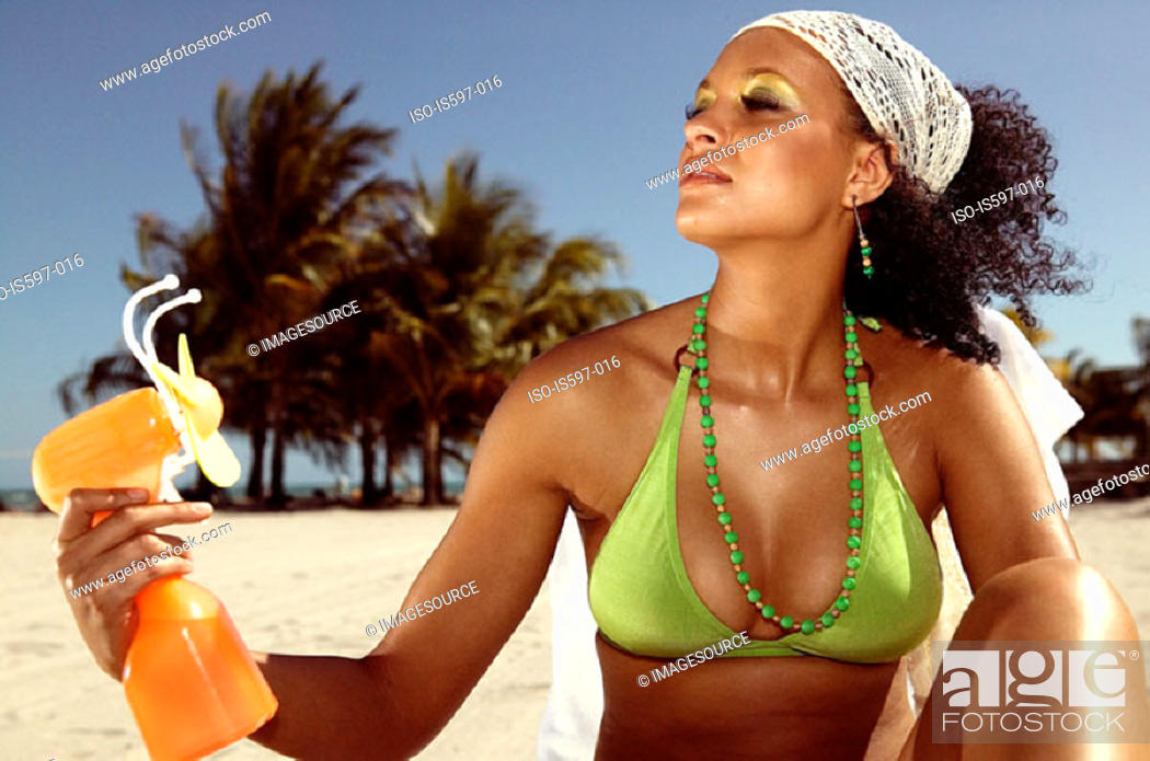 Stock Photo: Woman using fan on beach.