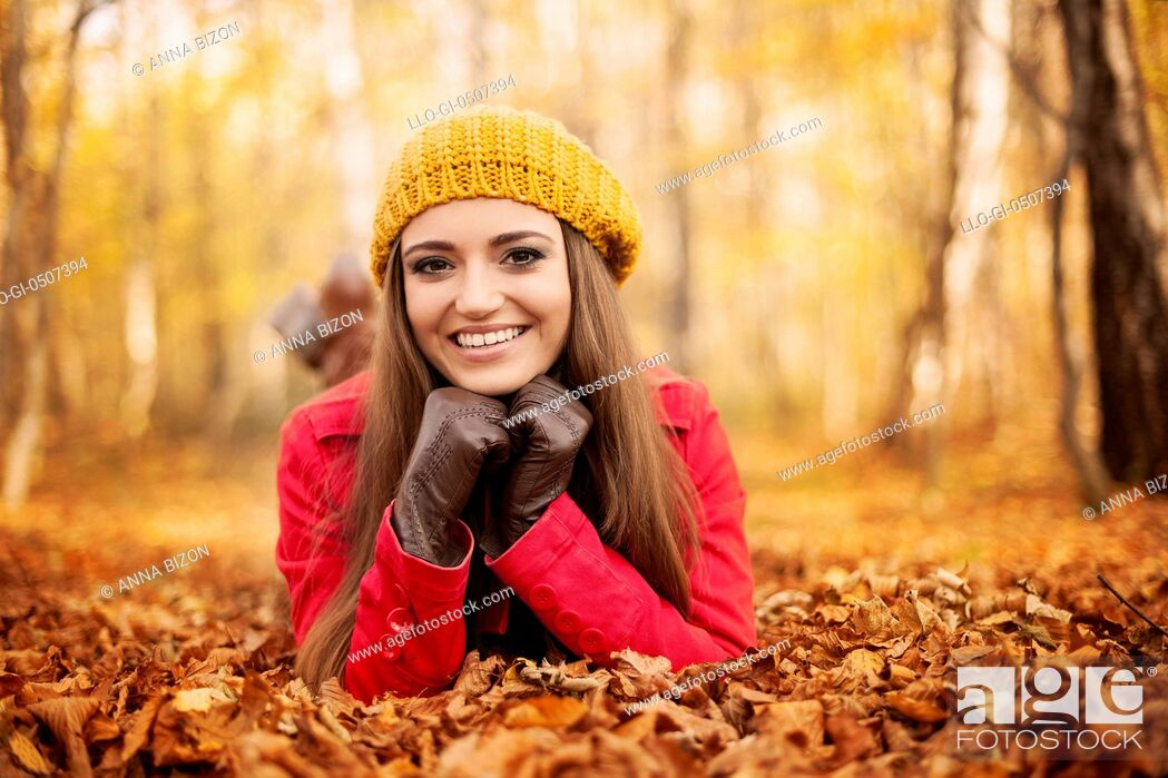 Stock Photo: Smiling woman lying down on autumn leaves, Debica, Poland.
