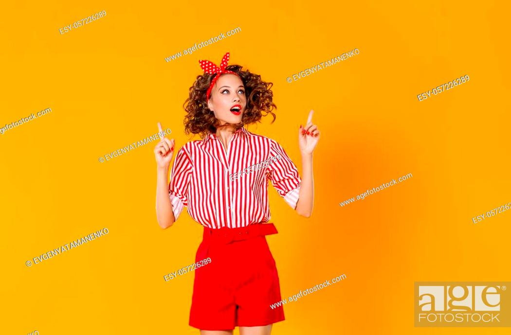 Stock Photo: young beautiful funny girl on colored yellow background.