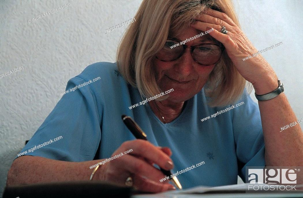 Stock Photo: elderly woman making notes.