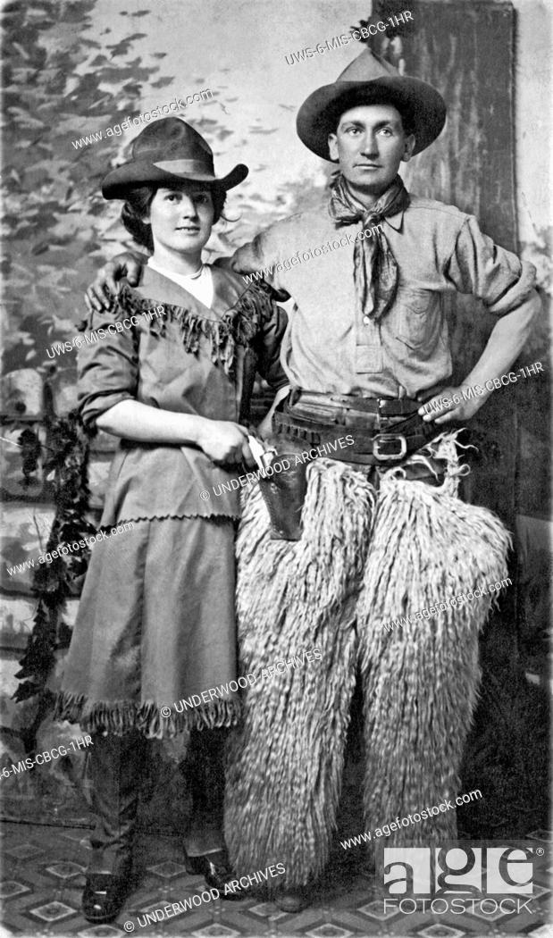 Stock Photo: United States: c. 1900.A couple pose for a studio portrait in Western cowboy gear.