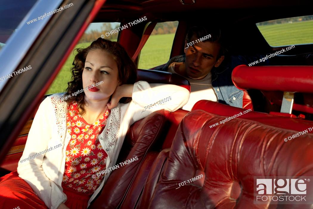 Stock Photo: A rockabilly woman and man sitting in a vintage car.