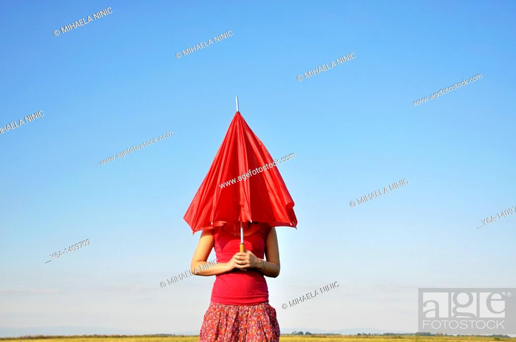 Stock Photo: Young woman holding red umbrella.