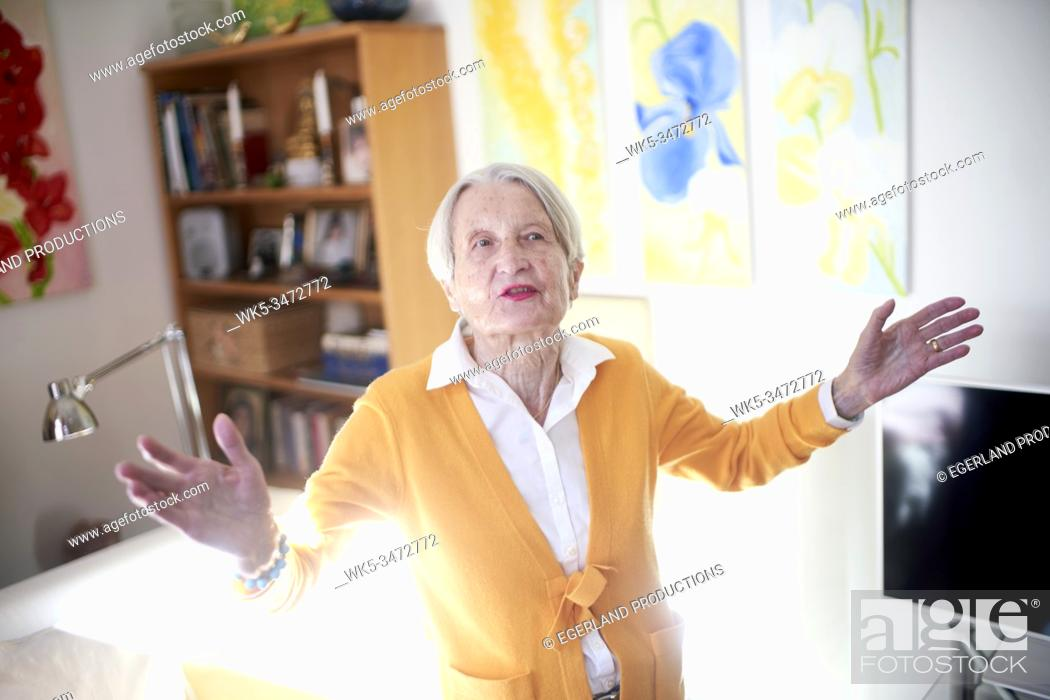 Stock Photo: artistic senior woman at home with arms open.