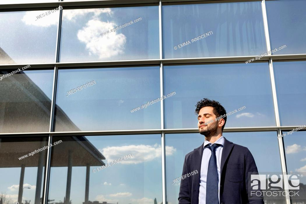 Stock Photo: Mid adult businessman standing with eyes closed in front of office building.