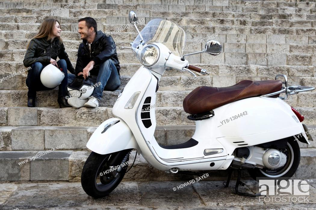 Stock Photo: Couple sitting on steps next to motor scooter.