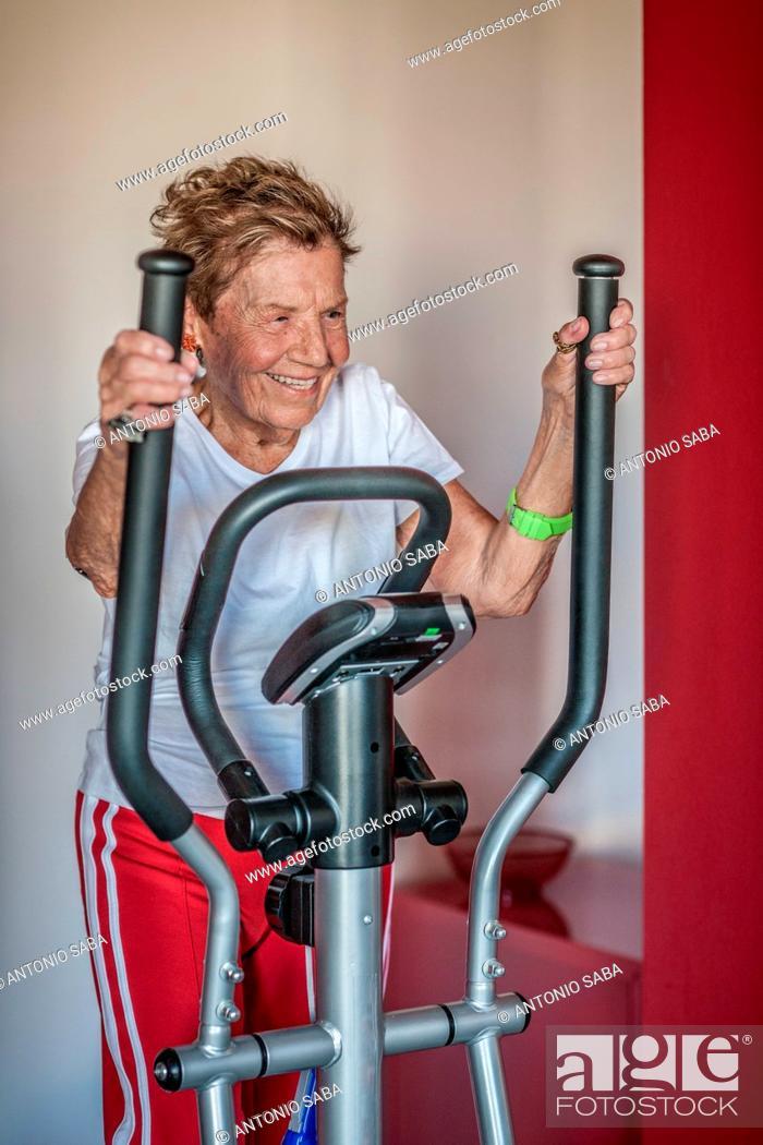 Stock Photo: A very senior woman using an exercise machine.