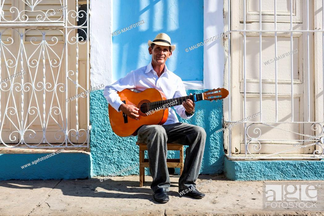 Imagen: Cuba, Trinidad, portrait of man playing guitar on the street.