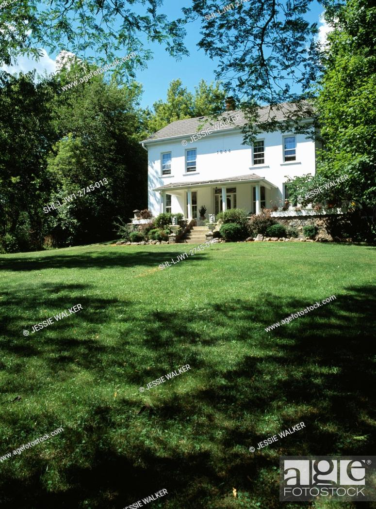 Stock Photo: EXTERIORS: Two story single family stucco 1840 farmhouse in a Georgian Colonial style, front porch with concrete steps, large lawn in front.