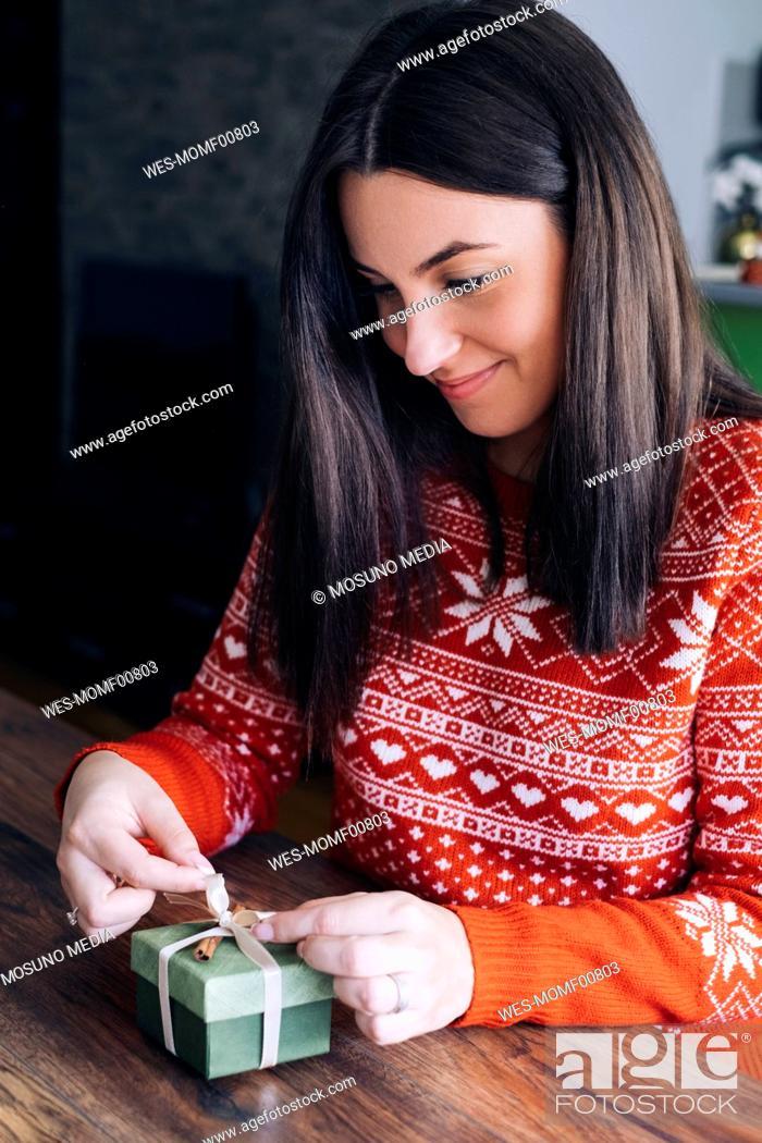 Stock Photo: Woman decorating Christmas present.