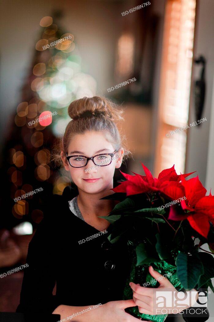 Imagen: Girl holding christmas poinsettia in living room, portrait.