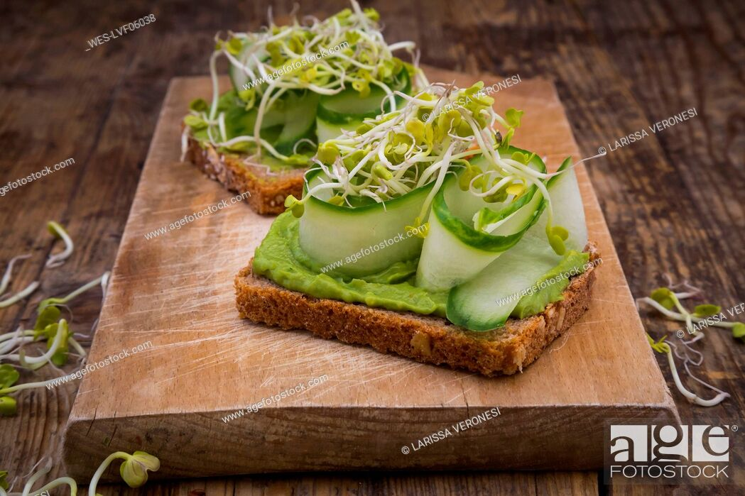 Stock Photo: Sandwich with avocado cream and cucumber garnished with radish sprouts.