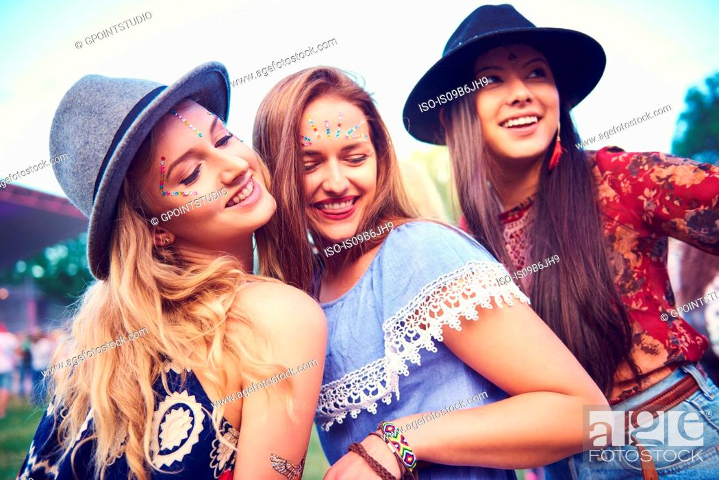 Imagen: Three young female friends in fedoras dancing at festival.