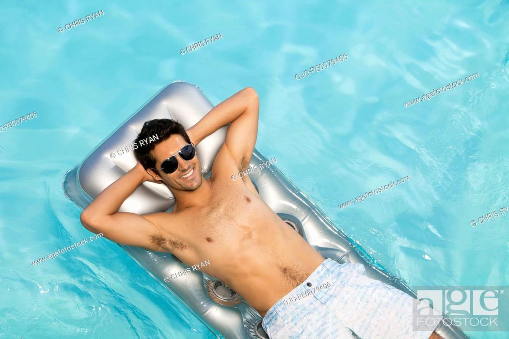 Stock Photo: Man floating in swimming pool sunbathing.