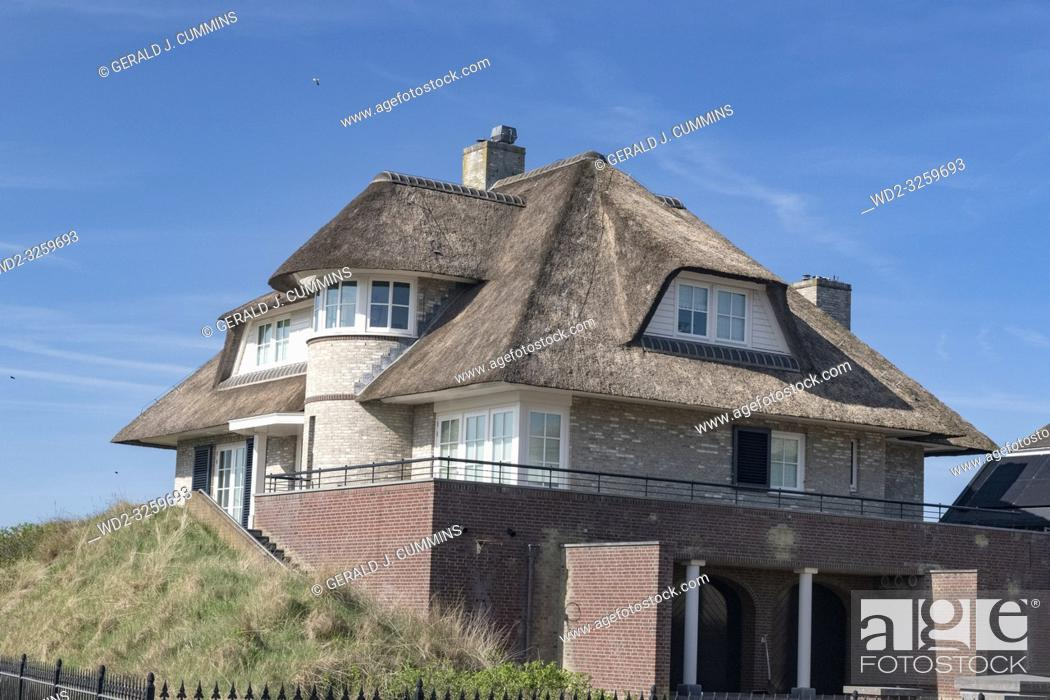 Stock Photo: Netherlands, zeeburg, 2017, An stunning example of a thatched roof on a red bricked house looking out over the north sea.