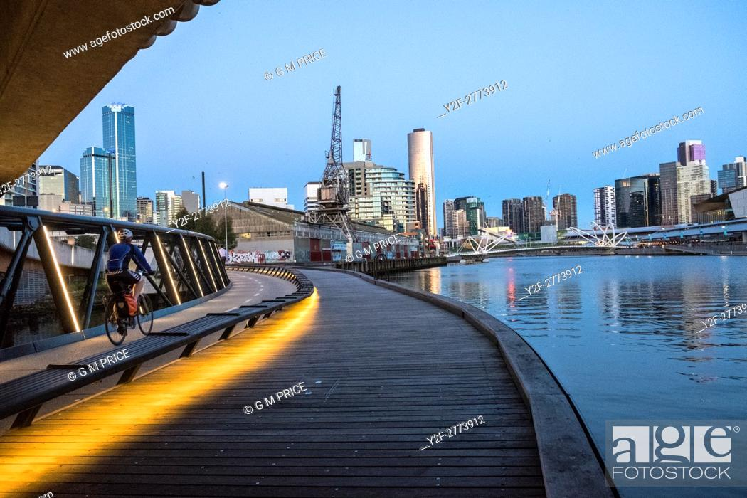 Stock Photo: Cyclist on Jim Stynes Bridge, below Wurundjeri Way, with view of Southbank, Melbourne.