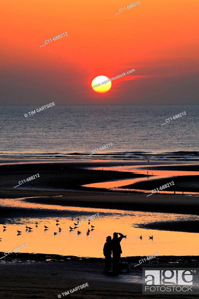 Stock Photo: Beautiful sunset over sea and beach with reflections in water and young couple holding hands watching sunset. Blackpool. Lancashire. England. UK.