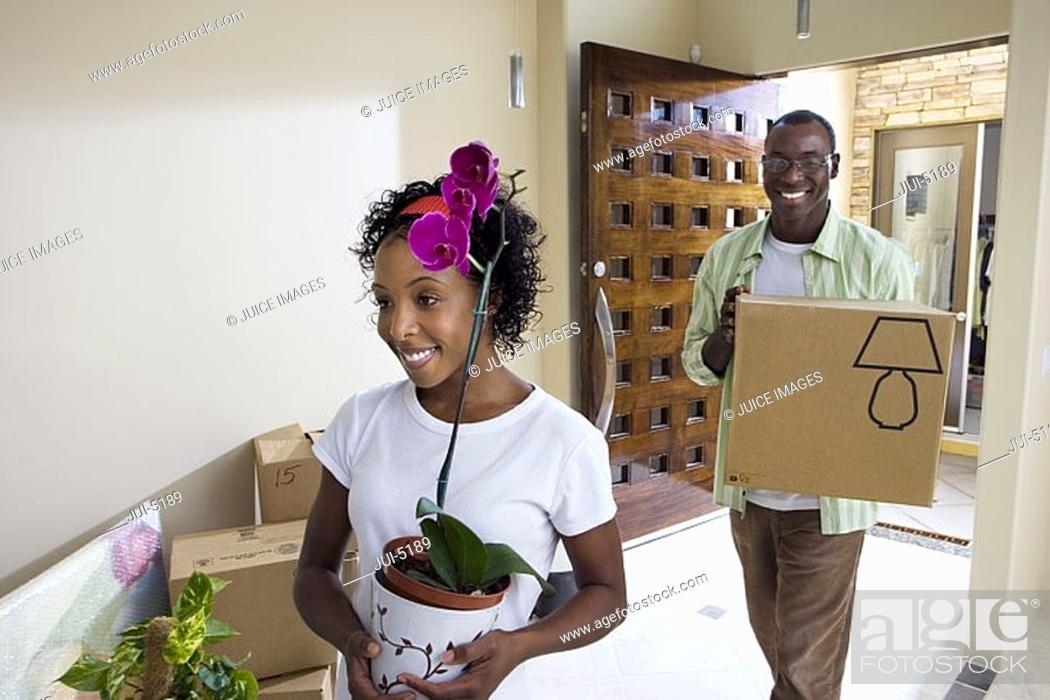 Stock Photo: Couple moving house, woman carrying plant pot, man carrying cardboard box in hallway, smiling.