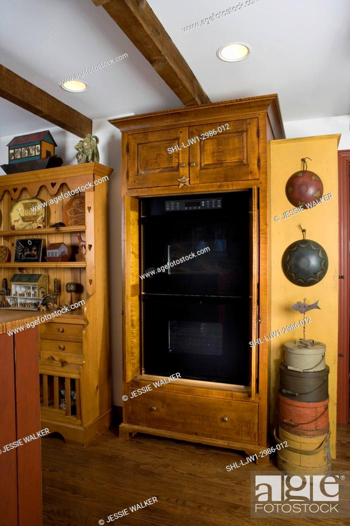 Stock Photo   KITCHENS: Double Ovens Are Hidden Behind Furniture Style  Cabinets By David Smith, Stack Of Wooden Handled And Painted Boxes,  Firkins, ...