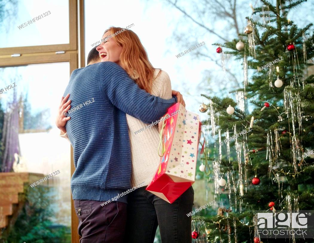Stock Photo: Couple standing in front of Christmas tree.