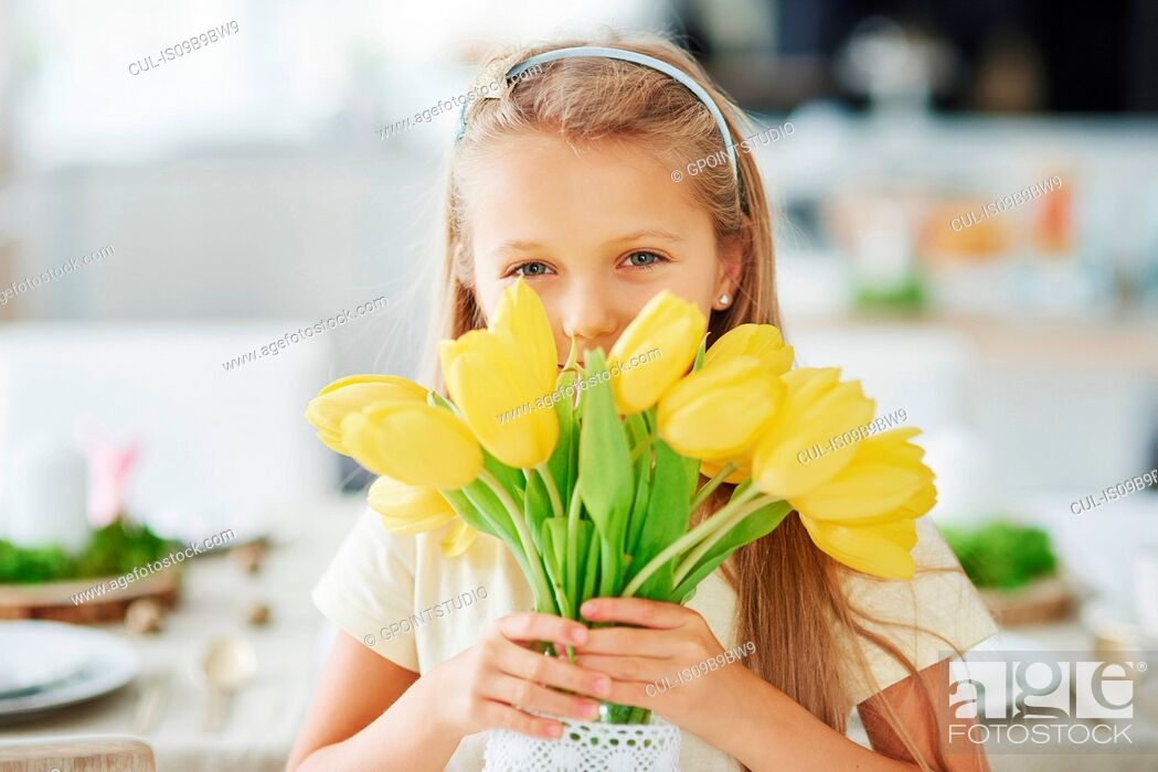 Stock Photo: Portrait of girl holding and hiding behind yellow tulips.