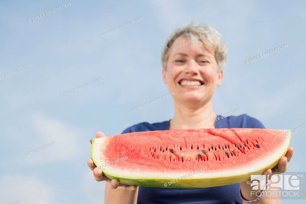 Stock Photo: Portrait of mature woman holding watermelon, smiling.