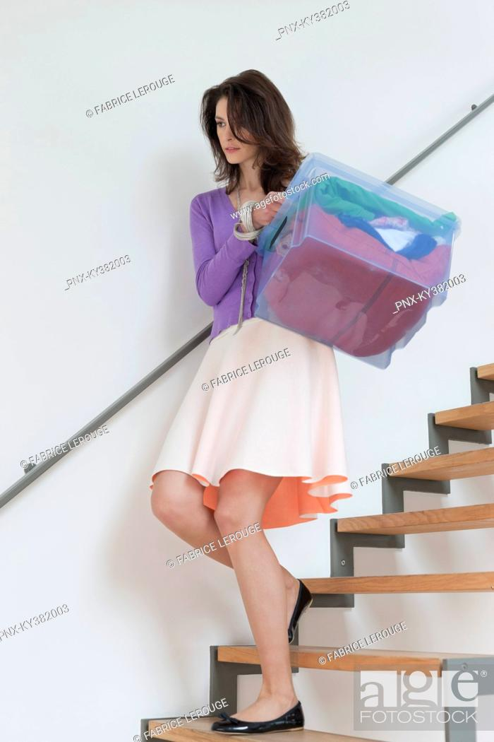 Stock Photo: Woman carrying a bucket of clothes.