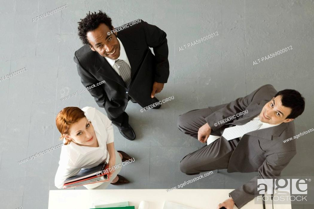 Stock Photo: Business colleagues in office, all smiling up at camera.