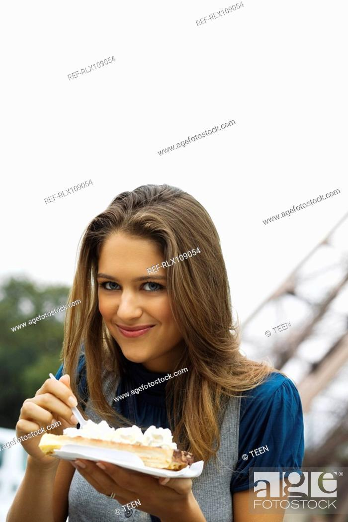 Stock Photo: Young woman eating cream covered Waffle in front of Eiffel Tower, Paris, France.