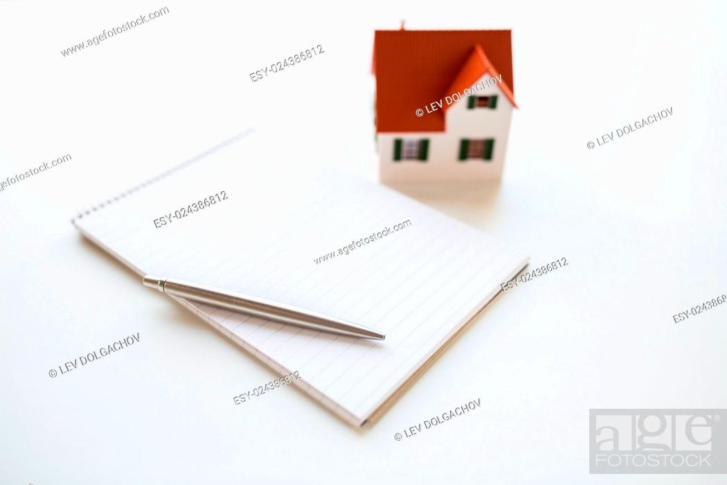 Stock Photo: building, mortgage, real estate and property concept - close up of house model, notebook and pencil.