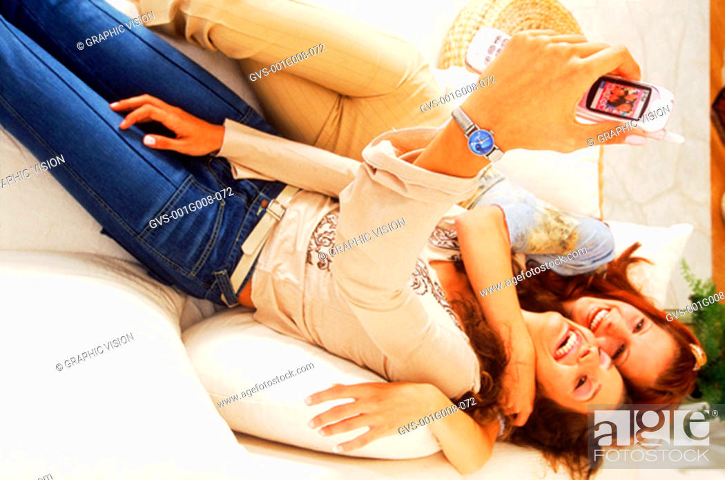 Stock Photo: Two young women lying in bed looking at a mobile phone.