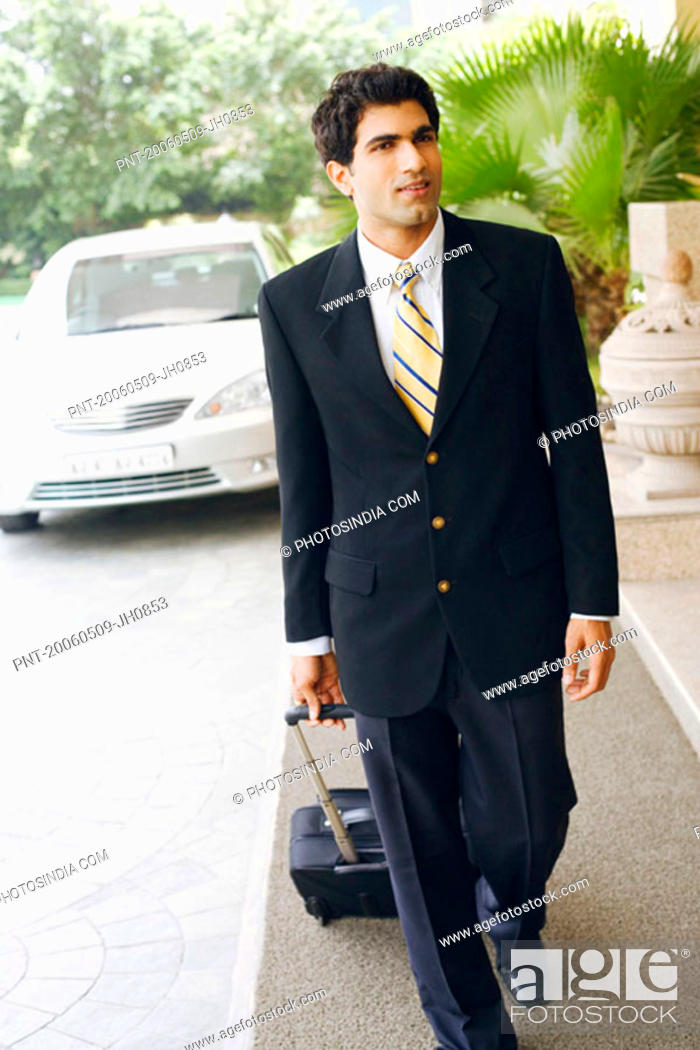 Stock Photo: Businessman walking with a suitcase.