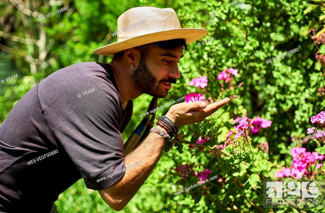 Stock Photo: Man smelling flowers in garden.