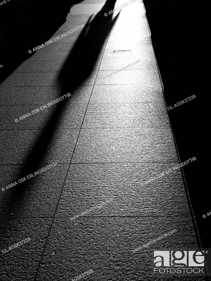 Stock Photo: Shadow of lonely figure walking along street.
