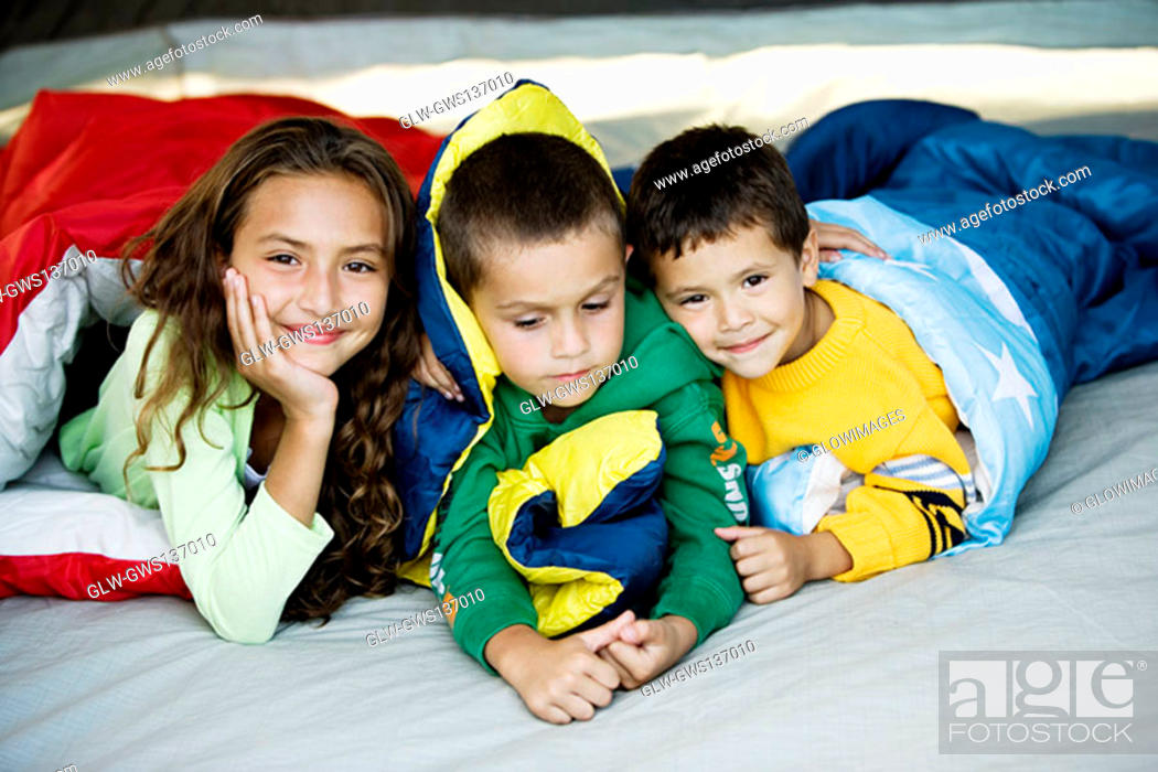 Stock Photo: Close-up of a sister and her two brothers lying on the bed.