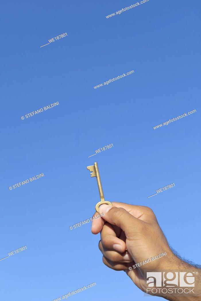 Imagen: Hand holding key against blue sky.