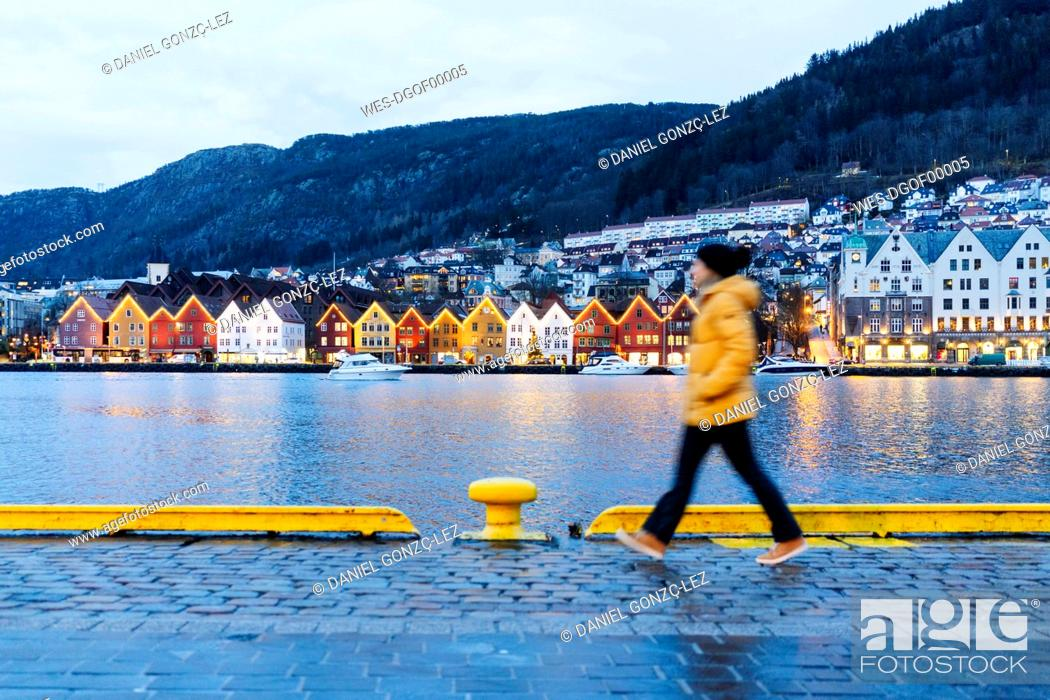 Stock Photo: Woman wearing a yellow jacket and walking at harbour in Bergen, Norway.