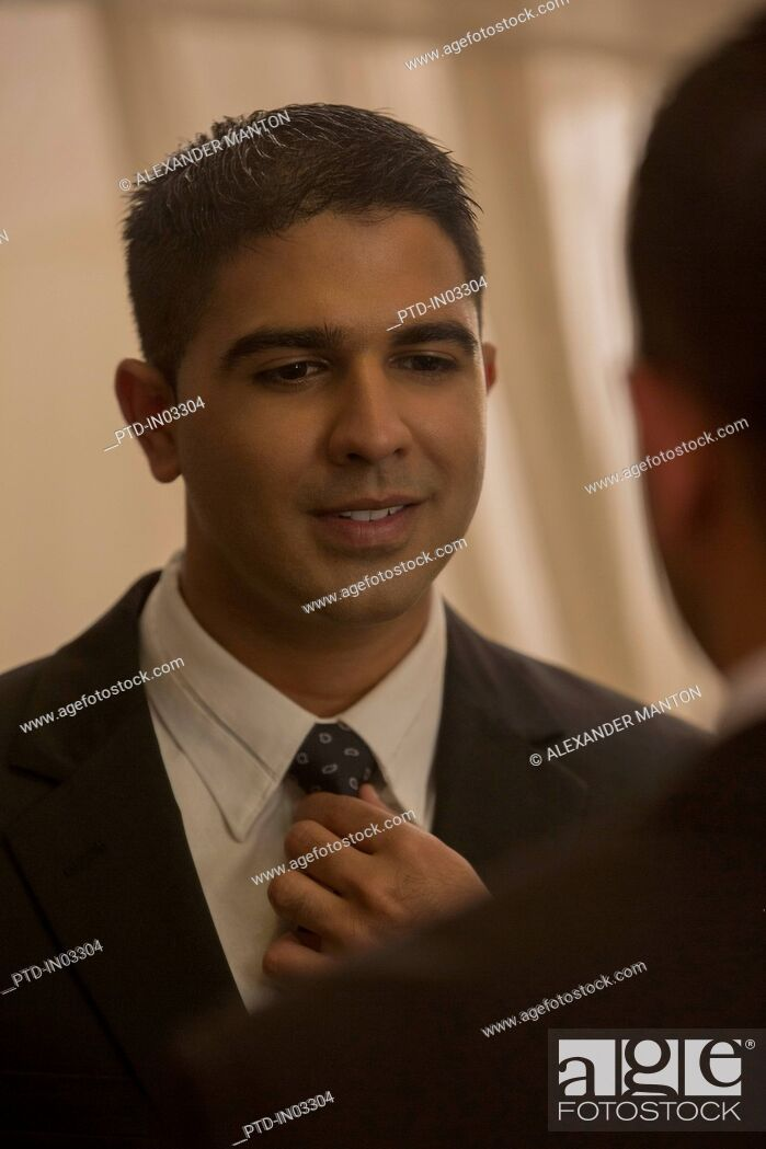 Stock Photo: Singapore, Man putting on tie in front of mirror.