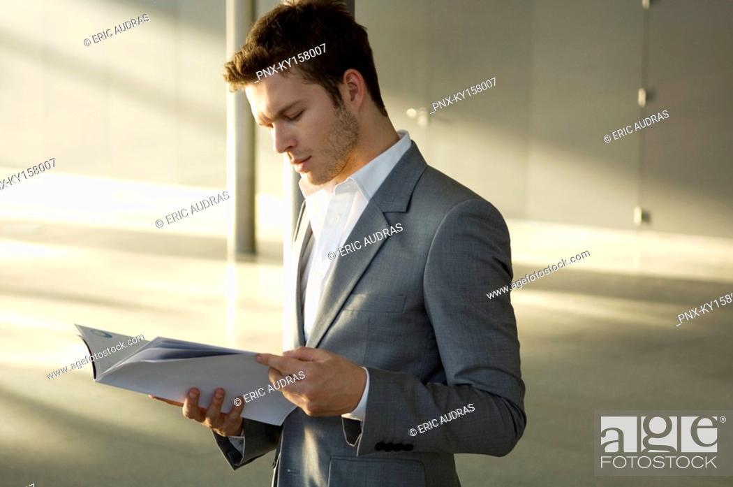 Stock Photo: Businessman reading a magazine.