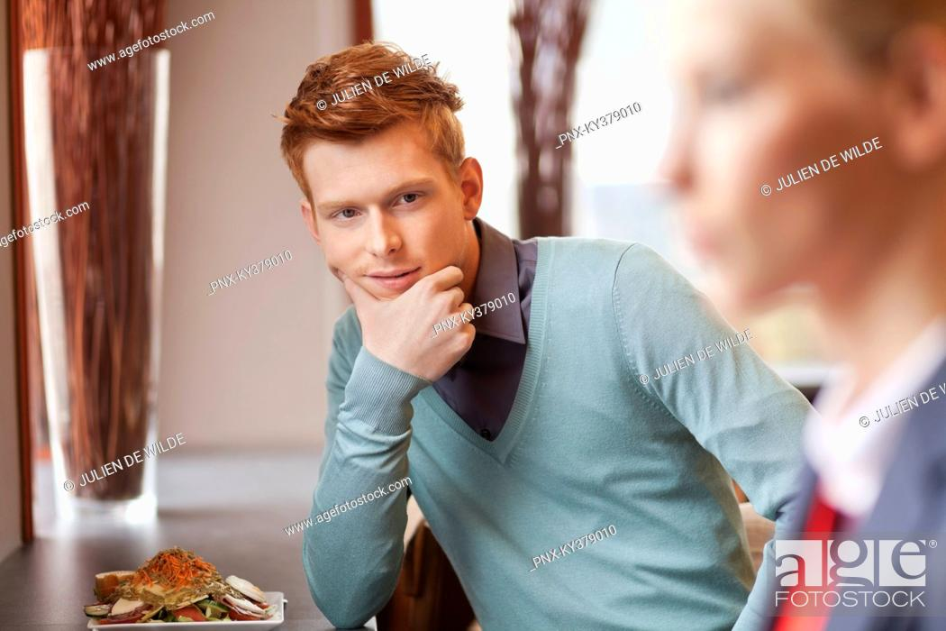 Stock Photo: Man in a restaurant looking at a businesswoman.