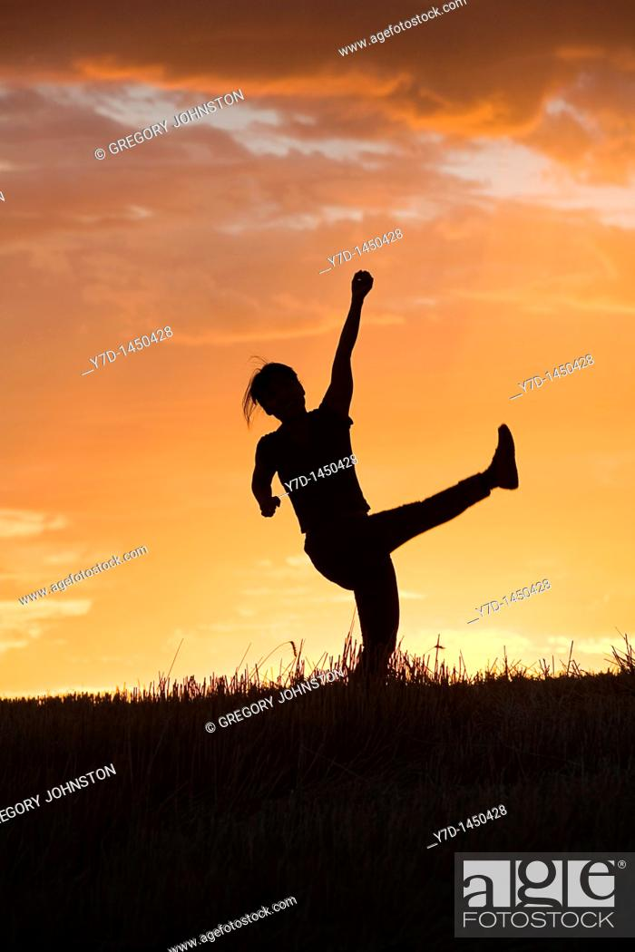 Stock Photo: A woman in the sunset light shows her happiness.