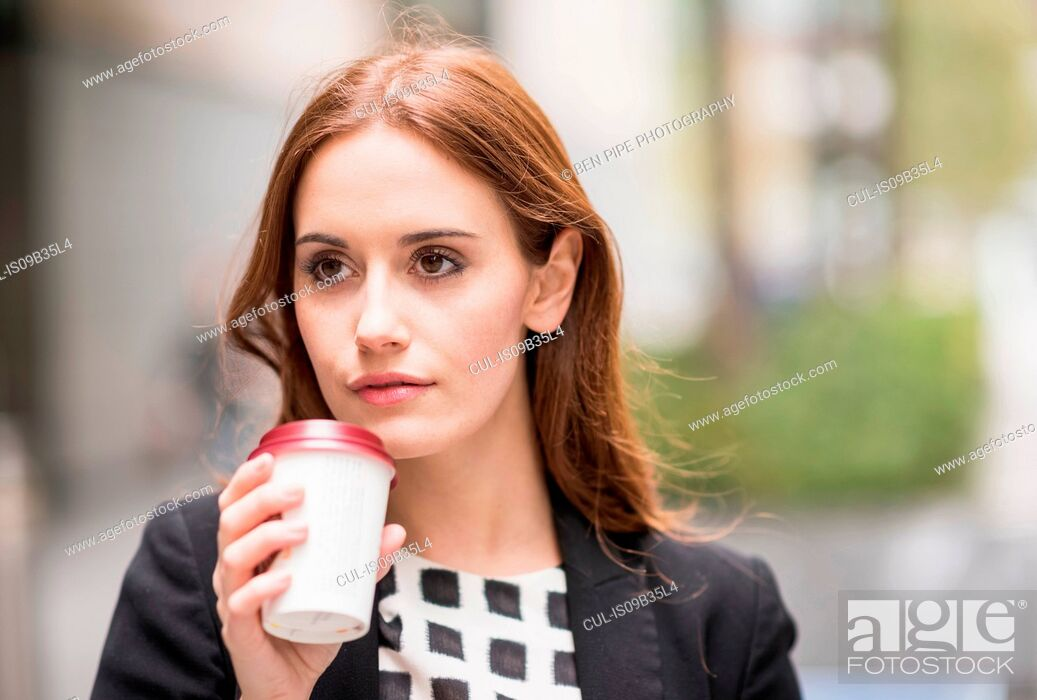 Stock Photo: Portrait of woman holding disposable coffee cup looking away.