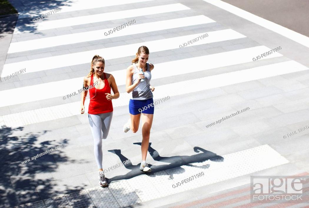 Stock Photo: Friends running across urban crosswalk.