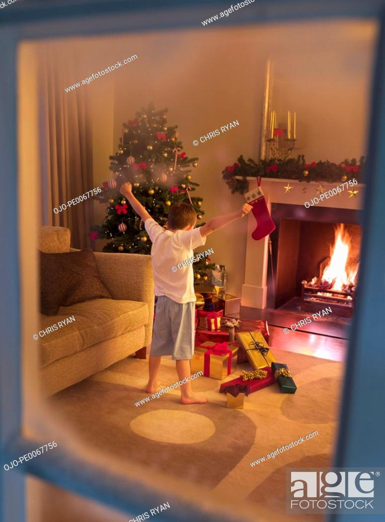 Stock Photo: Boy with arms outstretched in living room near Christmas tree.