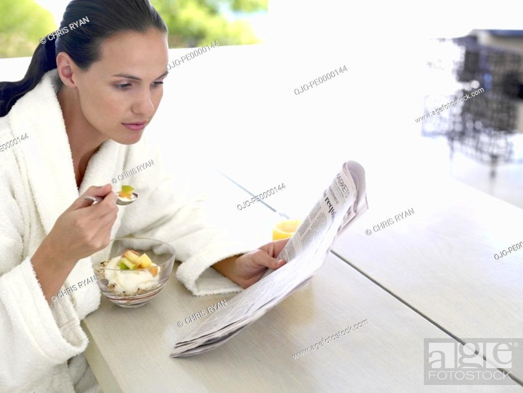 Stock Photo: Woman in robe eating healthy breakfast outdoors.