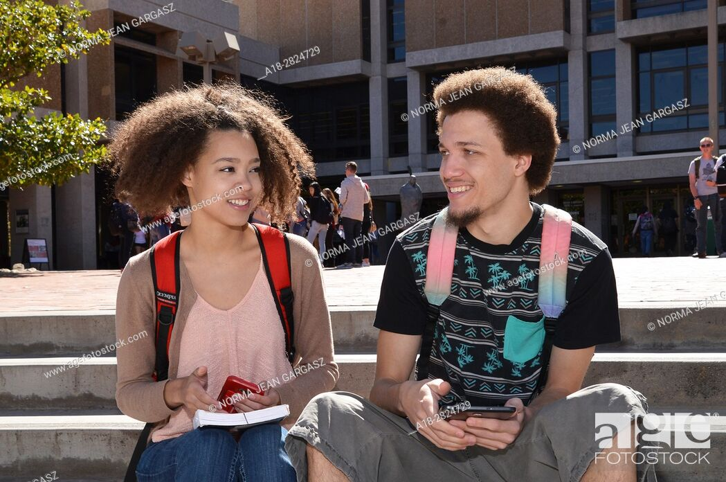 Stock Photo: A young woman and man with books and electronics on a college campus.